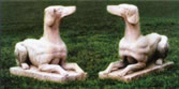 Two stone dogs sitting on the grass